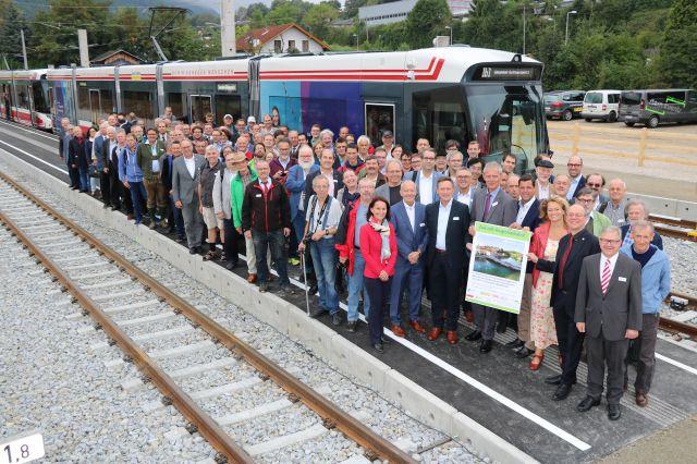 Foto bei der 7. Österreichische Regionalbahntagung in Gmunden; Teilnehmende mit Plakat vor Tram |  © Klimabündnis Österreich