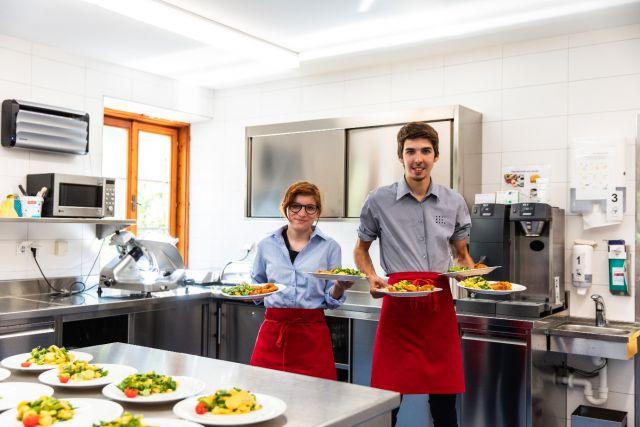 Ein Mädchen und ein Bub servieren Teller mit Essen in der Küche Foto: AufBauWerk