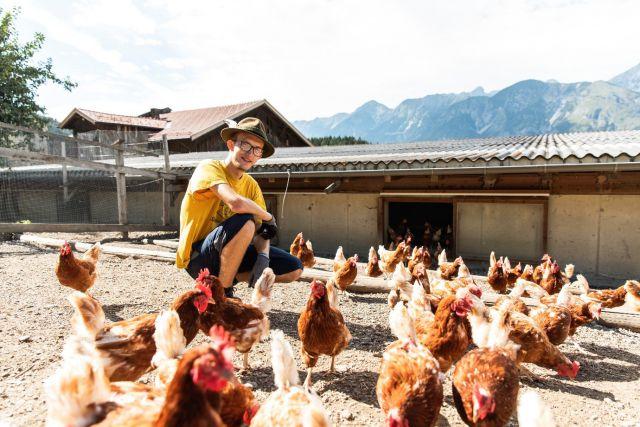 Ein Jugendlicher sitzt im Freilaufbereich des Hühnerstalls und ist von vielen braunen Hennen umgeben