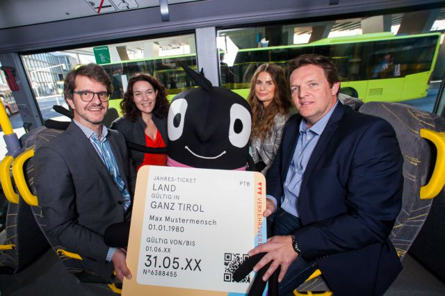 Vier Pesonen und das Maskottchen Edgar in einem Bus - Pressefoto