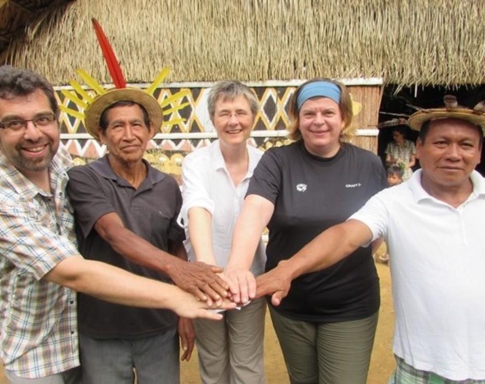 5 Personen reichen sich am Rio Negro die Hände.