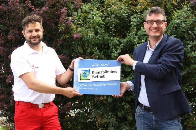 Andrä Stigger (rechts), Geschäftsführer von Klimabündnis Tirol, begrüßt Martin Klingenschmid, Geschäftsleiter der Bezirksstelle Innsbruck Land des Roten Kreuz, im Klimabündnis-Netzwerk. Foto: Klimabündnis Tirol