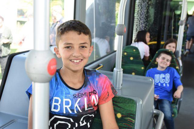 Kinder fahren mit einem Bus.