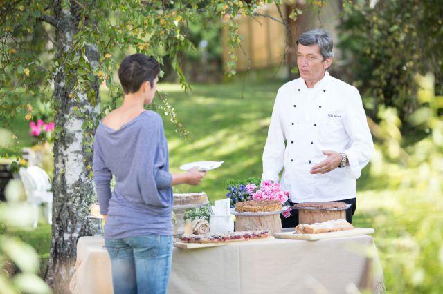 Frau im Garten am Buffet spricht mit Koch.