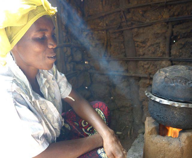 Frau mit einem Tuch am Kopf steht vor einer Feuerstelle mit Topf.