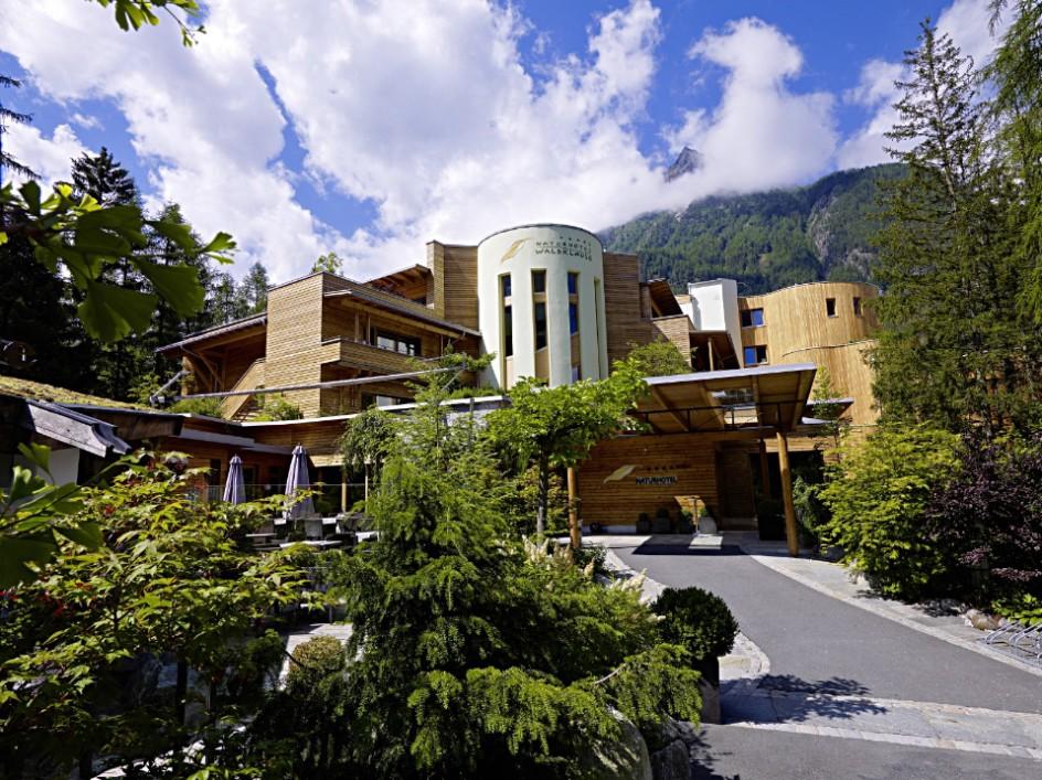futuristisches hotel mit baeume im vordergrund