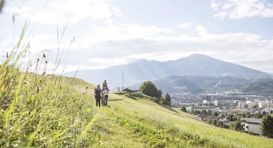Familie spaziert über grüne Wiese oberhalb von Innsbruck