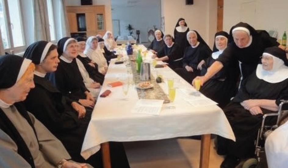 Tertiarschwester sitzen gemeinsam an einer Tafel