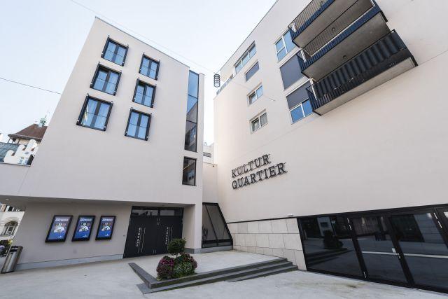 Hauptgebäude des BFI in Innsbruck; blühende Bäume; moderner Bau
