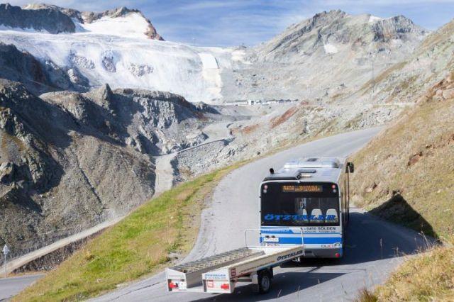 Öffentlicher Bus auf einer Bergstraße mit Fahrradanhänger