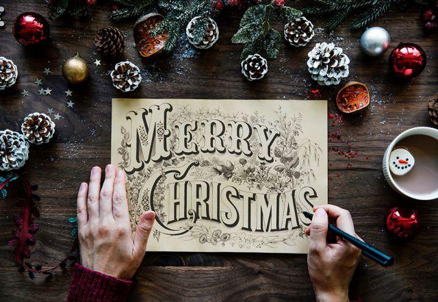 """Auf einem Tisch liegt eine Blatt mit der Aufschrift """"Merry Christmas"""", rundherum Tannenzapfen und Weihnachtsdekoration."""
